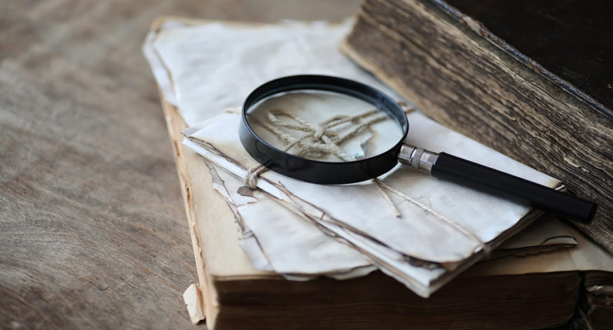 Old books on a wooden table and glass magnifier
